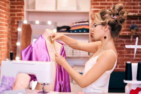 Foto de Mujer con maquillaje brillante con un interesante peinado en rollos de hilo y tijeras cabellos. La chica sostiene el pin con sus labios, mide la ropa, hace el patrón, llora las gafas, determina el tamaño en mannequin.. - Imagen libre de derechos
