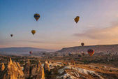 Hot air balloons flying  in the sunrise over mountain landscape