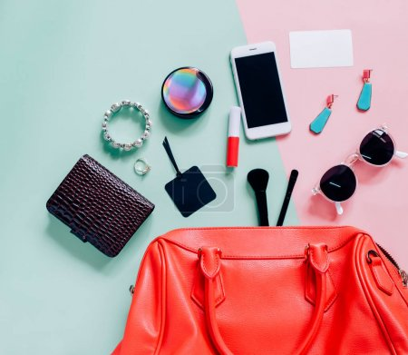 Flat lay of pink cute woman bag open out with cosm...