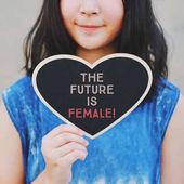 Inspirational motivation slogan the future is female on heart shape blackboard on girl hand, feminism quote