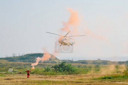 Photo for Man firing signal to helicopter in field - Royalty Free Image