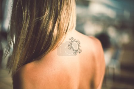 tanned woman with tattoo on her back