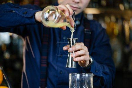 Bartender is making cocktail at bar.
