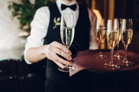 waiter brings glasses of champagne
