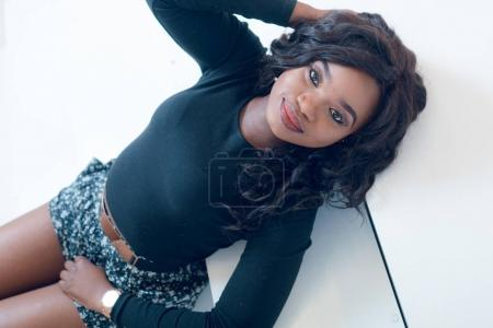 Beautiful young  African American woman in  shorts posing in studio