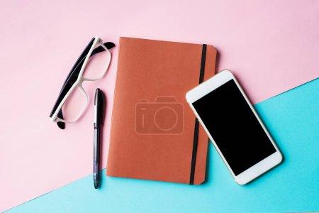 Photo pour Vue du dessus du bureau avec smartphone vide, bloc-notes et autres fournitures - image libre de droit
