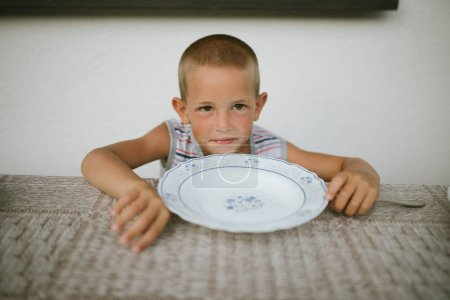 Portrait of boy at table with white plate