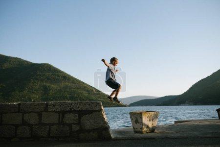 Boy playing at lake side