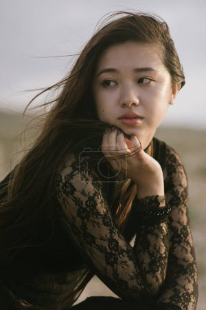young asian girl in black dress touching her long hair posing on nature background