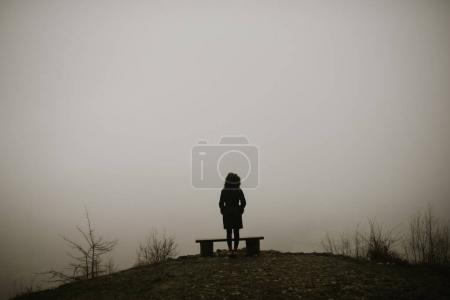woman standing on background of snowy and foggy forest