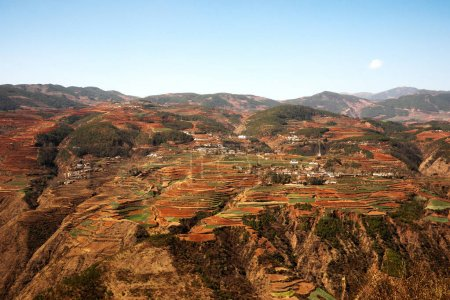 Panoramic view of chinese agriculture village landscape surrounded by red colored mountains.