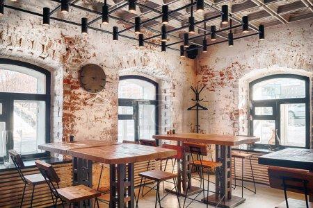 Photo pour L'intérieur d'un café loft moderne avec chaises et tables en bois et grandes fenêtres - image libre de droit