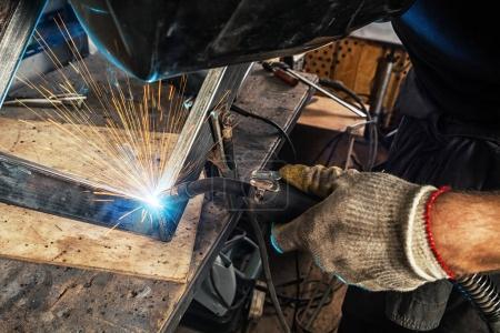 Photo pour Un jeune soudeur portant un masque de soudage noir et des gants de construction soude une machine à souder les métaux dans un atelier - image libre de droit