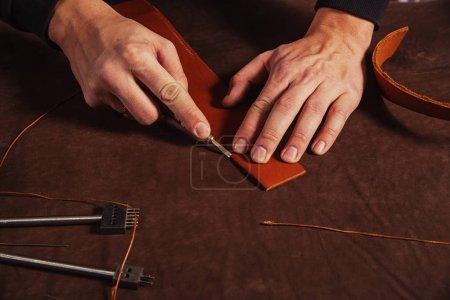 Photo pour Un gros plan d'un homme écumeur fait une ceinture en cuir véritable, coupe la peau avec un couteau spécial sur la table de la croûte, une vue de dessus - image libre de droit