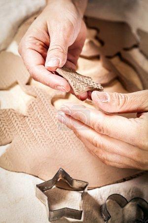 Photo pour Gros plan de femmes potier en argile roulée avec un moule sculpte jouets et les équipe avec des bords, dans le fond de l'argile et des formes - image libre de droit