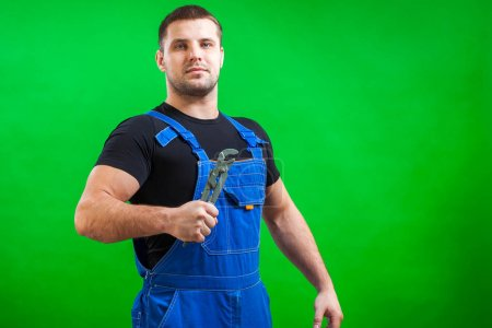 Young man builder worker in a black T-shirt and blue construction overall holds a new gray tool  straight pipe wrench on a green isolated background