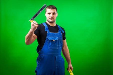 Photo pour Un ouvrier de la construction aux cheveux foncés dans un T-shirt noir et une construction bleue tient globalement la règle carrée de l'angle de forme r L et un niveau magnétique rare sur un fond vert isolé - image libre de droit