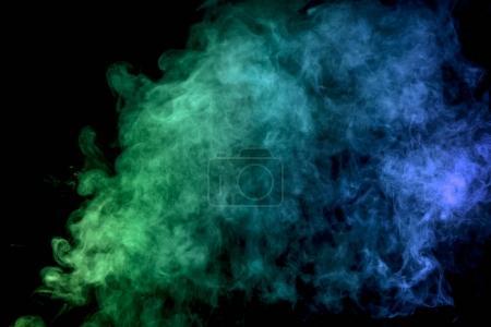 Photo pour Fumée épaisse et colorée de bleu et de vert sur un fond isolé noir. Contexte de la fumée de vape - image libre de droit