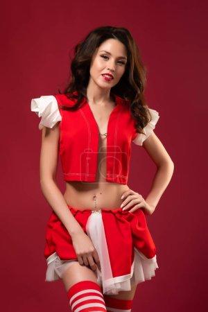 Neujahrsporträt einer jungen Frau im hübschen Weihnachtsmann-Kostüm in gestreiftem Golf, die charmant lächelt und auf rotem Hintergrund posiert. Charmante Frau für weihnachtliche Designs