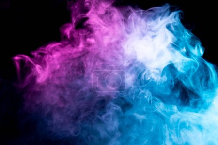 Photo for Fog colored with bright pink and blue gel on dark background.Frozen abstract movement of  explosion smoke multiple colors on black background. - Royalty Free Image