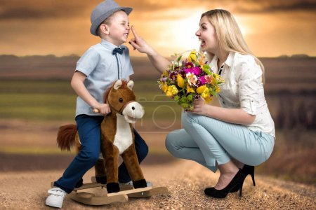 The son on the horse, gives a basket of flowers beloved mother.Little Prince on horseback.Spring ,women's day