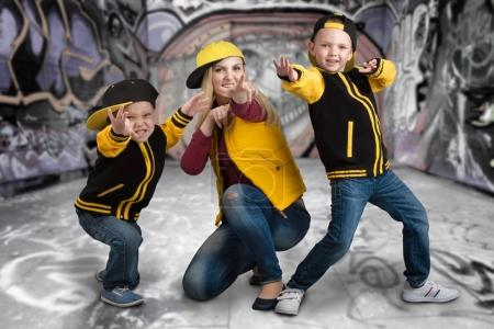 A young mother and two young sons in the style of hip hop.Fashionable family.Graffiti on the walls.