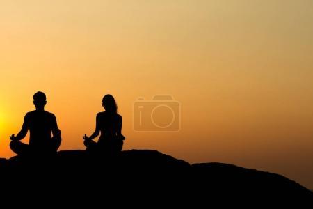 Photo pour Silhouette de séduisantes confiant à moitié nu homme et femme, faire du yoga sur rocher plage de remise en forme de bien-être yoga zen méditation l'esprit corps formation, sain heureux relax sourire, soleil magnifique plage set - image libre de droit