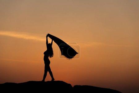 Photo pour Silhouette de moitié homme femme confiante nue faire une pose de liberté face au soleil sur un sol rocailleux un soleil mis ciel près de la plage pour boire la réalisation, la liberté, surmonter, concept de performance de résultat - image libre de droit