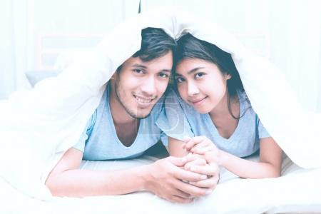 Mixed race lovers concept. Young white male in his bedroom getting intimate with his pretty young chinese girlfriend under the blanket. Wearing blue jeans, shirt and in their early twenties.