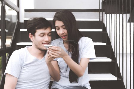 Mixed race lovers concept. Young white male taking selfie with his pretty young chinese girlfriend on a stairs. Wearing blue jeans, blue shirt and in their early twenties. Taken indoor.