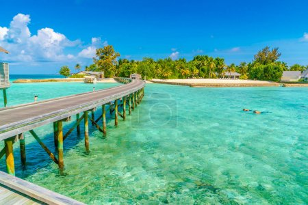 Beautiful water villas with couple snorkeling  in tropical Maldi