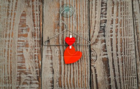 Red paper heart hanging on wood background .