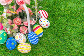 Velikonoční vajíčka s umělou květinou na čerstvé zelené trávy