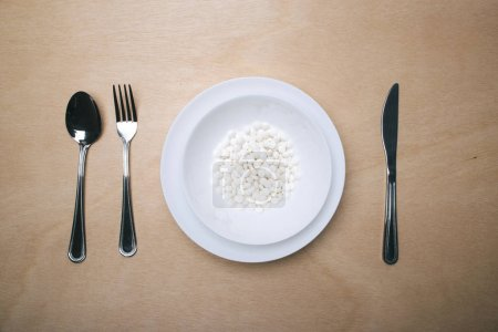 plate full of pills with cutlery on wooden table