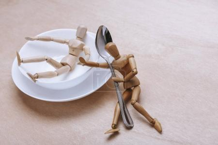 wooden mannequins with cutlery and bowls