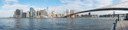 New York city skyline panorama and Brooklyn Bridge, sunny day