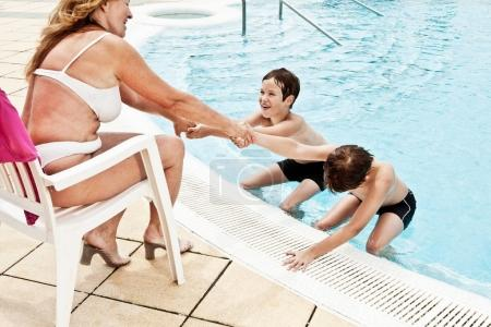 boys coaxing grandmother into pool