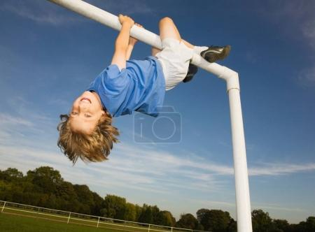 Boy hanging off goal post