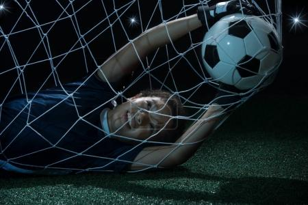 boy holding ball in goalpost