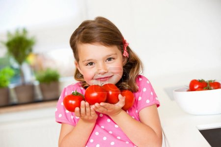 Girl with tomatoes smiling at camera
