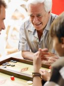 Boy playing backgammon with father and grandfather