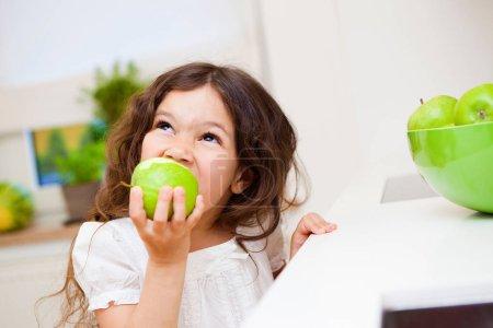 Girl biting green apple