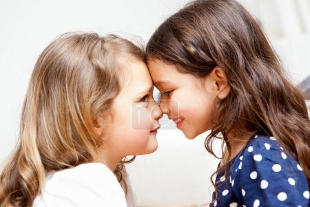 Two little girls rubbing noses