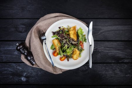 Photo for Salad with salmon in breadcrumbs with lettuce and sesame seeds, served with cutlery on the white plate, pepper grinder and linen napkin with wooden background. Top view. - Royalty Free Image