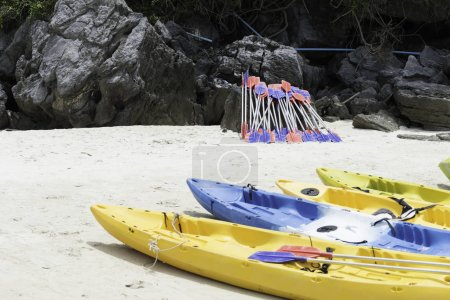 Paddles and colorful kayaks on white sand beach in sunny day,Tha
