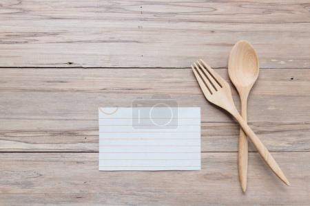 Cuillère en bois et un mémo menu blanc sur fond de bois