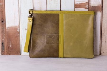 Vintage leather bag on grunge wooden background