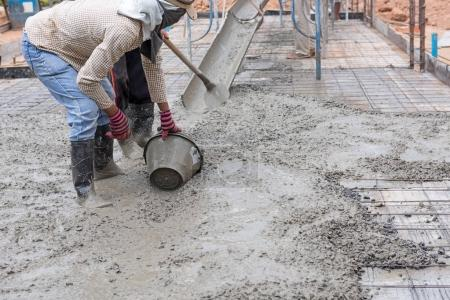 Construction workers spreading freshly poured concrete mix for h