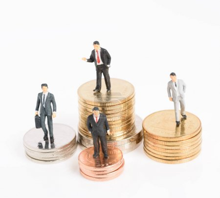 Miniature business people stand on money coins isolated on white