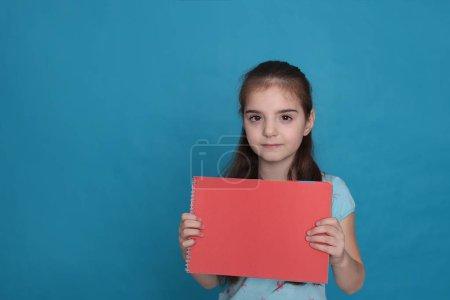 Chica alegre amorosa de ocho años y una hoja de papel de color espacio libre para grabar sobre un fondo azul